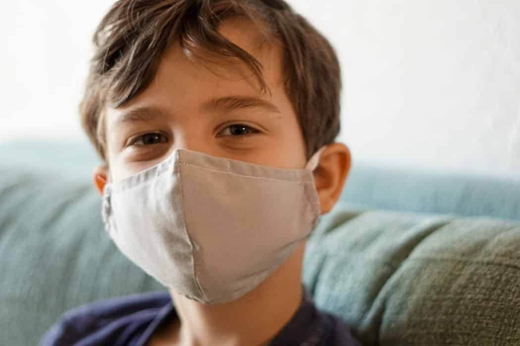 kid smiling behind a face mask